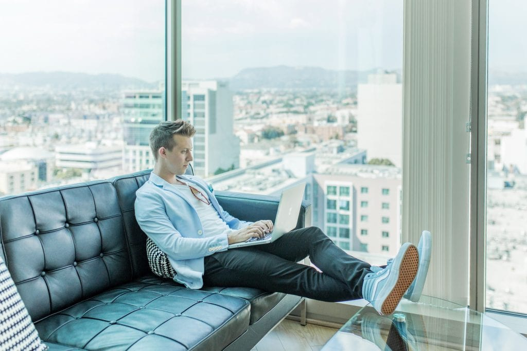millennial in high rise office building working on laptop