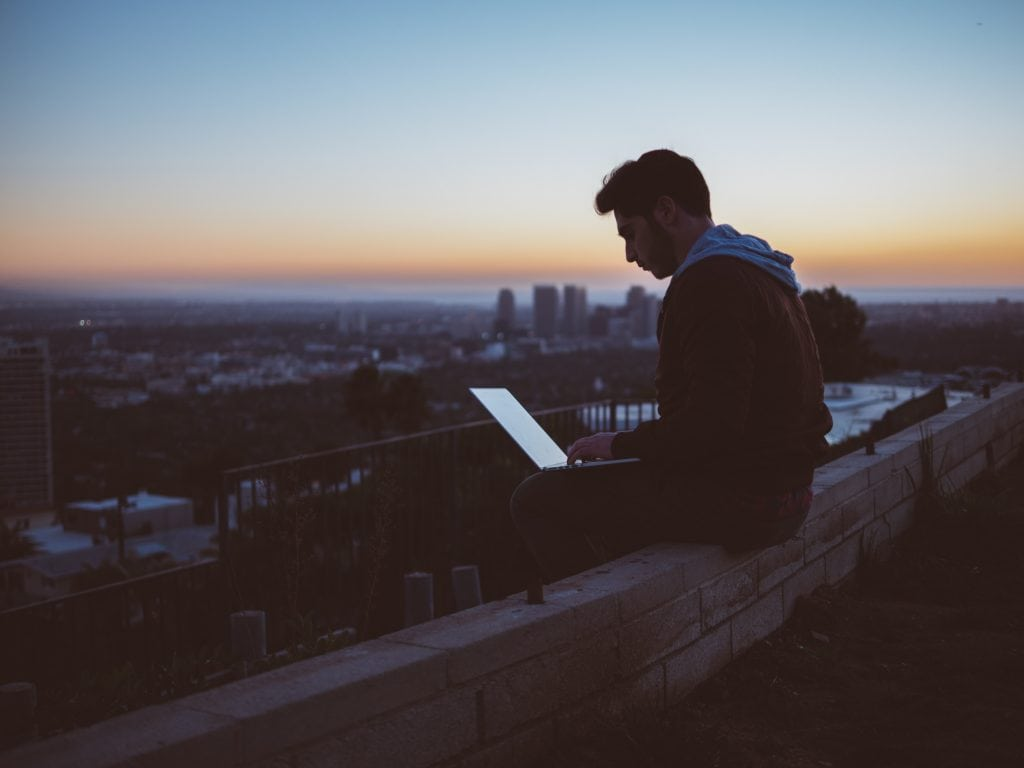 Boy sitting on laptop sunset traveling