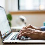 hands blue shirt typing keyboard writing on laptop