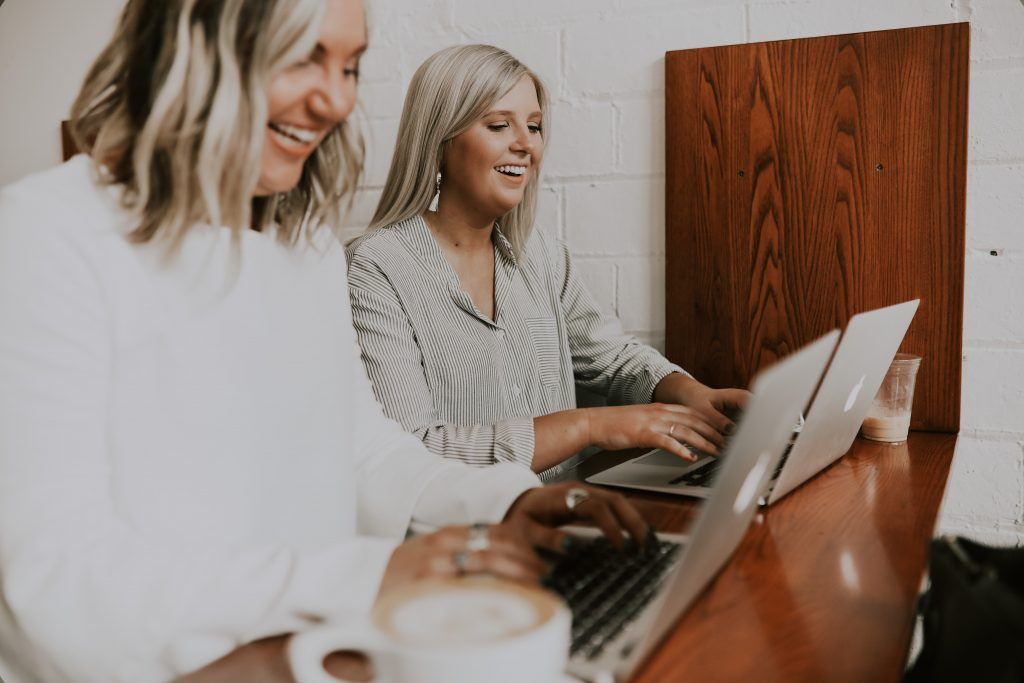 two girls laptop writing laughing smiling