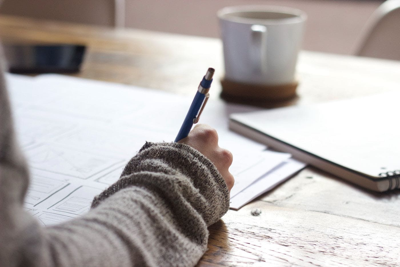 author writing with pen and paper freelance writing